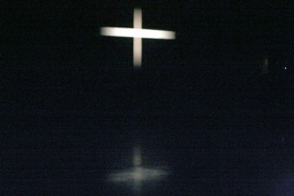 A white cross projected on a screen is reflected on a shiny floor below