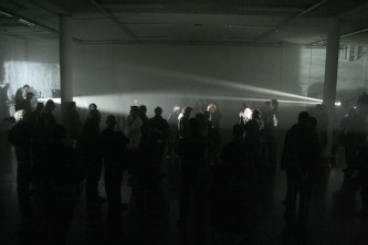 A room of people caught between two projectors