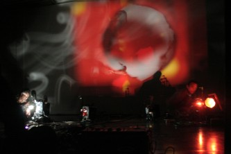 Swirling red and orange projection in a room of projectors