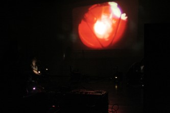 A red form projected on a wall in a darkened room