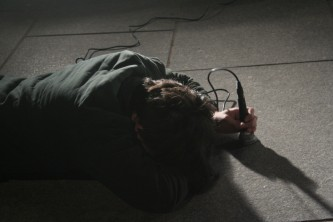Participants lie on the floor outside hitting microphones on the floor