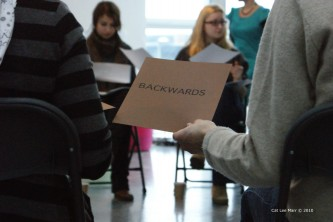 Someone passing a piece of paper that says 'backwards' on it