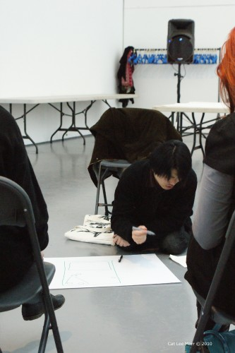 Taku Unami writing on a piece of paper on the floor