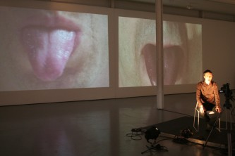 Christof Migone sticks his tongue out, screens projecting it in the background