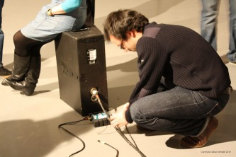 Loic Blairon kneels by a DI box and a monitor on the floor