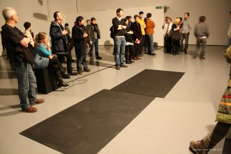 Two blackboards on the floor and audience stand around