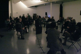 in a dim gallery space people are sat on randomly positioned chairs