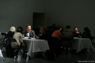 several tables with people talking into microphones