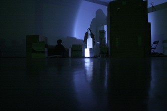 A shadow in the background amongst mic stands and boxes, one light source