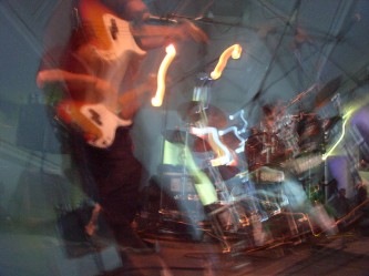 A blurry long exposure of a guitarist playing on stage