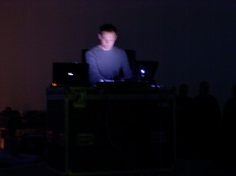 Carston Nicolai with electronic equipment lit from a laptop screen