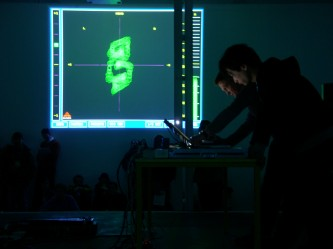 Cyclo performing in front of a projection of a computer game screen