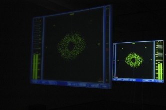 Two hanging screens showing data from a computer