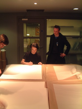 A large table with large sheets of paper and 2 people signing them