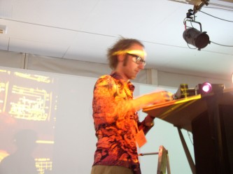 a man in a loud orange shirt operates a slide projector