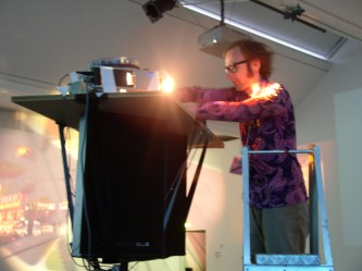 A man at the top of a ladder operates a slide projector