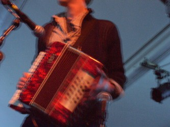 Someone holding an accordion near microphones