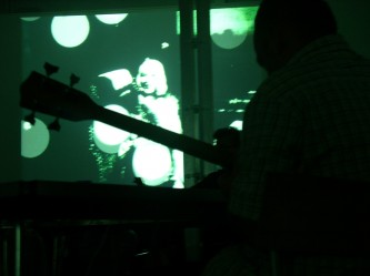 a bass guitar in silhouette against a projection of a green image