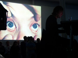 An audience beneath an image of a person's eyes