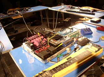 A table covered in guitar pedals and cables, a pedal steel guitar