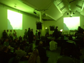 a large room lit with green light many musicians + audience
