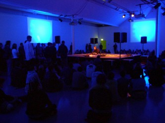 Steve Roden on a platform in the middle of a room surrounded by audience