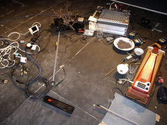 Steve Roden's pedal steel guitar, bowl of straw, pedals, mixer, branch