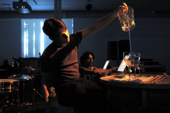 a man pouring water from a jug into a vessel during a performance at KYTN 03