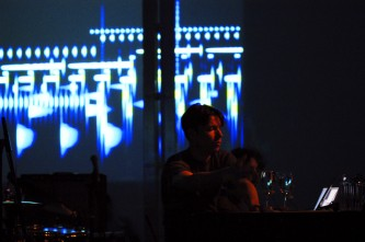 A man seated at a table in front of a screen of projections