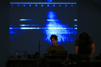 [The User] performing Silophone at KYTN 03 in front of a screen of blue forms