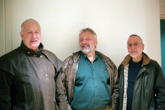 John Tilbury, Malcolm Le Grice and Eddie Prevost standing near a wall