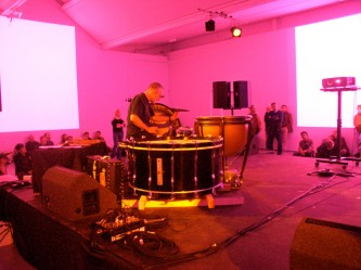 Eddie Prevost playing a large horizontal bass drum in pink light