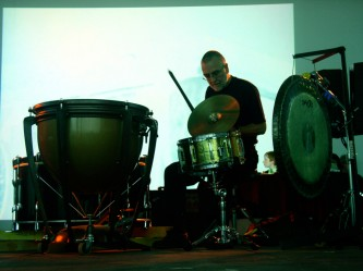 Eddie Prevost bowing a cymbal near a snare drum in front of a projection