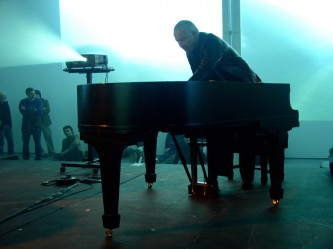 John Tilbury playing a piano in a room full of projections