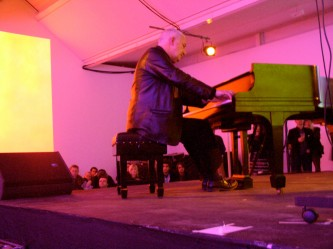 John Tilbury playing a piano in a room full of pink light