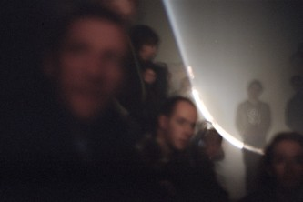 A cross section of a cone of light seen above an audience in darkness