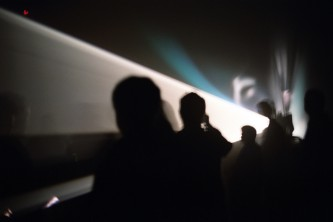 A cone of light among audience members in silhouette