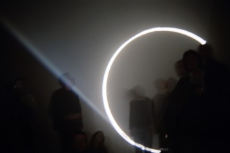 A circle of light from a projector circles audience members