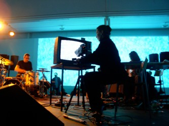 Burkhard Beins playing drums Ulrike Flaig with a tv and video camera