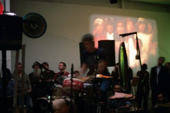 Tim Barnes playing drums near a projection at KYTN 04