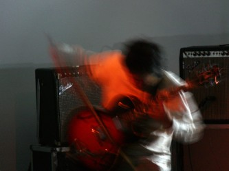 Kazuo Imai blurred with movement bowing an electric guitar