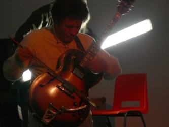 Kazuo imai bowing a gibson archtop guitar with flourescent tube behind