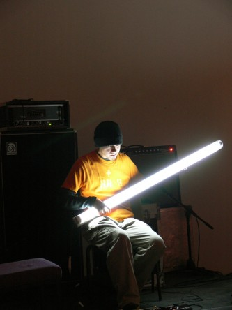 Atsuhiro Ito sitting with illuminated flourescent tube in front of an amplifier
