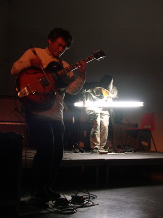 Kazuo Imai and Astuhiro Ito on stage with guitar and light bulb