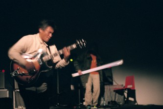 Kazuo Imai and Astuhiro Ito on stage with guitar and flourescent tube