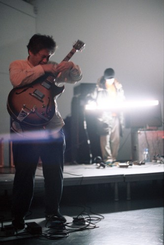 A man playing electric guitar in front of a man playing flourescent tube