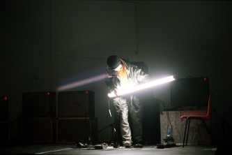 Atsuhiro Ito with illuminated flourescent tube in front of amplifiers