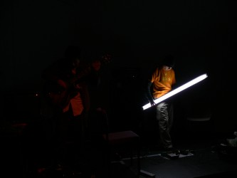 A man lit by a  hand held flourescent tube steps on a pedal in the dark