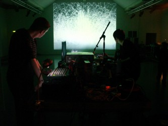 Two performers either side of a projector and desk, a screen in the distance