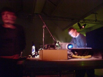 A blurred image of two people working with projection equipment